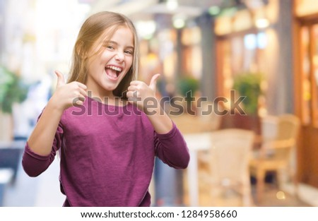 Young beautiful girl over isolated background success sign doing positive gesture with hand, thumbs up smiling and happy. Looking at the camera with cheerful expression, winner gesture. #1284958660