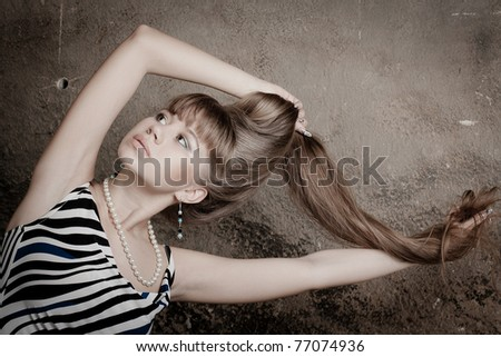 young beautiful girl plays with the long hair