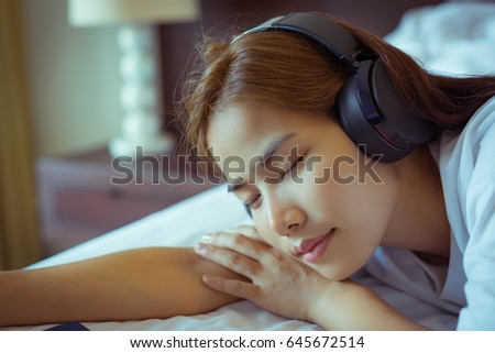 Young beautiful girl portrait wearing headphones in the room.