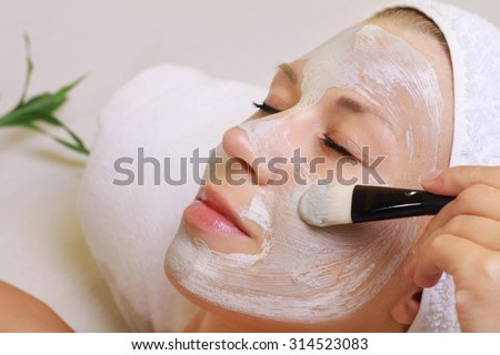 Young beautiful girl receiving clay facial mask in spa beauty salon.  Skin care, Beauty treatments.