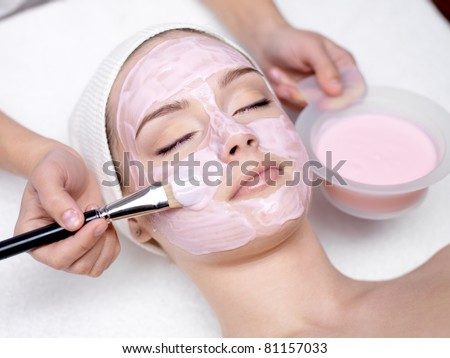 Young beautiful girl receiving pink facial mask in spa beauty salon indoors