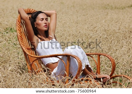 young beautiful girl relaxing in a chair in the field