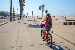 Young beautiful girl riding a bike down the Venice beach in Los Angeles. Californian dreaming.