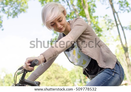 Young beautiful girl riding a white bicycle in the park #509778532