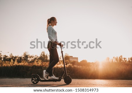 Young beautiful girl riding an electric scooter in the summer on the street, against the sunset, there is free space for advertising against the sky