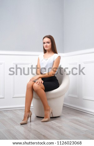 Young beautiful girl sits on a white round armchair in full growth, business style clothes, high heel shoes, leg on leg, looks at the camera. A series of photos #1126023068