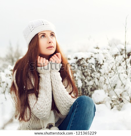 Young beautiful girl sitting in snow