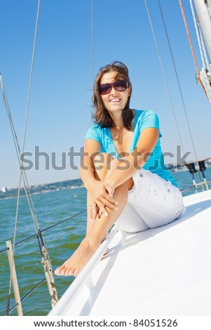 Young beautiful girl sitting on a yacht