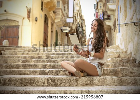Young beautiful girl sitting on the stairs reading  - Shutterstock ID 215956807