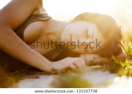 Young beautiful girl sleeping in nature, under the sun.