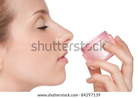 Young beautiful girl smell cream jar