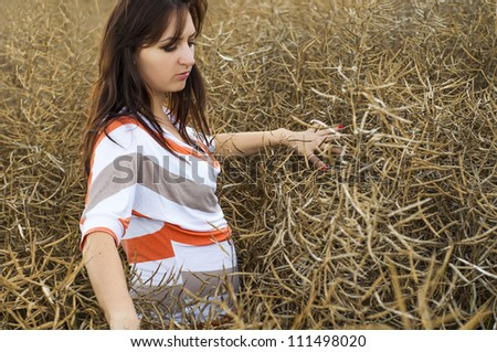 Young beautiful girl standing in the rape field