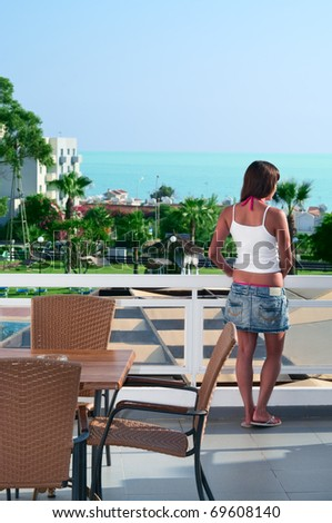 Young beautiful girl standing on the balcony of the hotel and looking into the distance. One Caucasian woman is back side