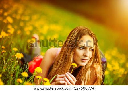 Young beautiful girl student lying on a grass. Summer field with yellow flowers dandelion