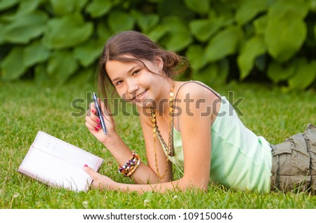Young beautiful girl studying in the park, lying on grass