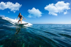young beautiful girl surf on the big waves in the open ocean. Mauritius Island
