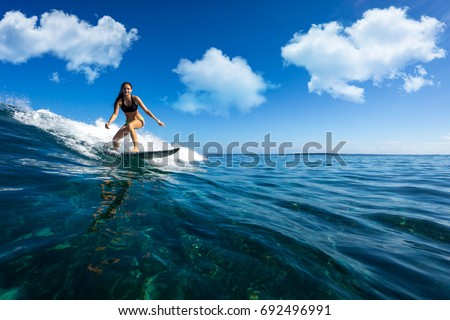 Stock Photo young beautiful girl surf on the big waves in the open ocean. Mauritius Island