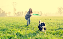 Young beautiful girl throwing to her dog in a park at sunset - Asian woman playing with her dog