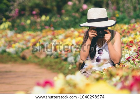 young beautiful girl tourist travel taking picture in flower garden weekend holiday lifestyle park outdoor nature background, photography journey backpack adventure outdoor with copy space.