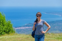 Young beautiful girl traveler with striped shirt, backpack and sunglasses looking at camera, smile and posing at Olympus mountain, aerial view of Aegean sea, valley and blue sky, vacation in Greece