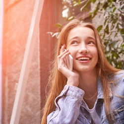 Young beautiful girl using phone. Smiling female person. Laugh woman portait. Student ourdoors waiting coffee. Morning conversation. Lady talking with friend. Happy model. Teenager with cellphone