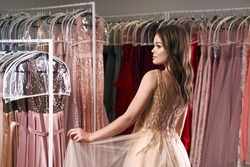 Young beautiful girl wearing a full-length beige yellow chiffon slit prom ball gown decorated with golden sparkles and sequins. Fashion model in dress hire service with many dresses on background.