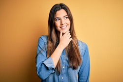 Young beautiful girl wearing casual denim shirt standing over isolated yellow background with hand on chin thinking about question, pensive expression. Smiling with thoughtful face. Doubt concept.