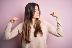 Young beautiful girl wearing casual turtleneck sweater standing over isolated pink background showing arms muscles smiling proud. Fitness concept.