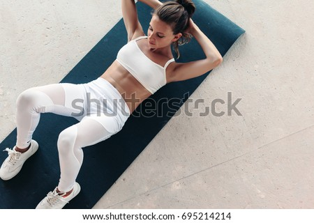 Young beautiful girl wearing fashion sports wear doing exercise on mat at loft gym, top view