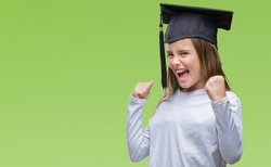Young beautiful girl wearing graduate cap over isolated background very happy and excited doing winner gesture with arms raised, smiling and screaming for success. Celebration concept.