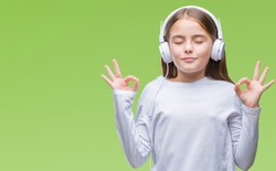 Young beautiful girl wearing headphones listening to music over isolated background relax and smiling with eyes closed doing meditation gesture with fingers. Yoga concept.