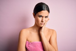 Young beautiful girl wearing towel shower after bath standing over isolated pink background thinking looking tired and bored with depression problems with crossed arms.