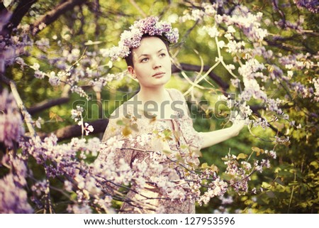Young beautiful girl wearing wreath in the garden among a spring blossom.
