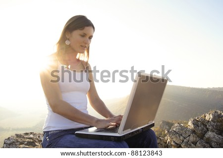 Young beautiful girl with a laptop in the sun