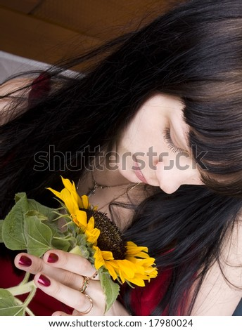 young beautiful girl with a sunflower in hands