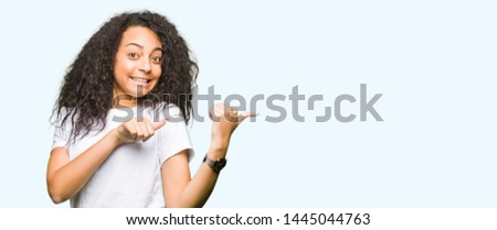 Young beautiful girl with curly hair wearing casual white t-shirt Pointing to the back behind with hand and thumbs up, smiling confident #1445044763