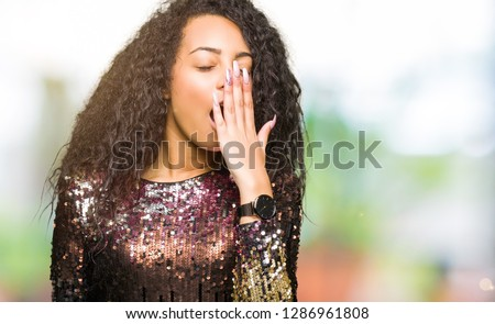 Young beautiful girl with curly hair wearing night party dress bored yawning tired covering mouth with hand. Restless and sleepiness.
