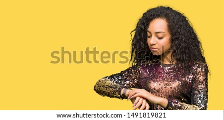Young beautiful girl with curly hair wearing night party dress Checking the time on wrist watch, relaxed and confident