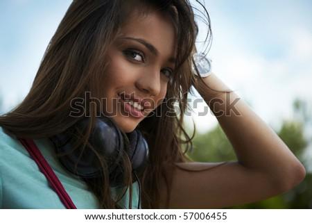 Young beautiful girl with earphones smiling. Outdoor photo.
