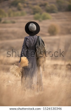 Young beautiful girl with in long trendy designer check dress black and white with a bouquet of yellow spikelets stands and enjoys nature