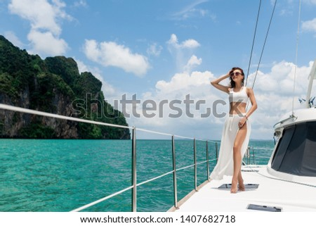 Young beautiful girl with long hair standing on the bow of the yacht in white skirt and bikini. Horizontal pictures