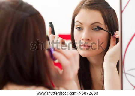 Young beautiful girl with makeup making her eyes with mascara to look sexy and gorgeous