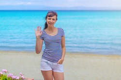 Young beautiful girl with striped t-shirt and white shorts posing and show hello on sandy beach, turquoise water of Toroneos gulf in Halkidiki Kassandra, sunny summer day, woman on vacation in Greece
