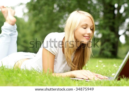 Young beautiful girl with the notebook laying in a grass