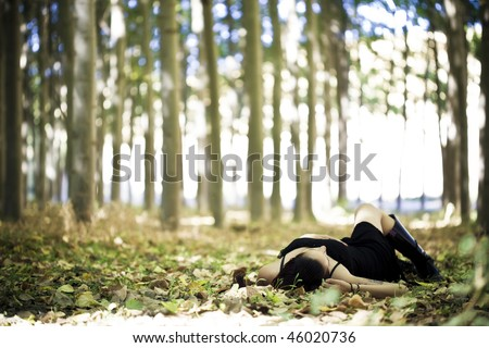 Young beautiful goth girl laying over the foliage.