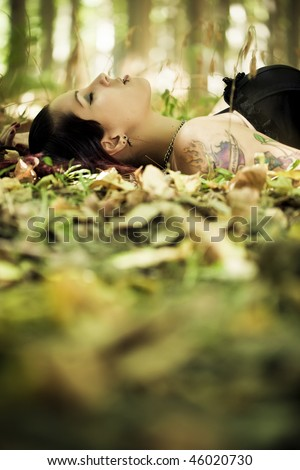 Young beautiful gothic girl laying over the foliage. - stock photo