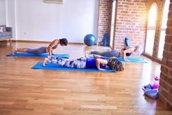 Young beautiful group of sportswomen practicing yoga doing upward-facing dog pose at gym