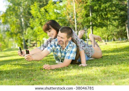 Young beautiful guy and the girl, lay on a lawn,  Photographed  each other, on cellular phones.