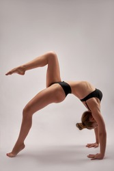 Young beautiful gymnast in sports clothes. Training, gymnastics element, acrobatics on a white background. Sports motivation, stretching, banner for advertising