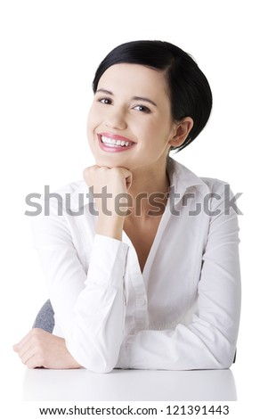 Young beautiful happy businesswoman behind the desk, isolated